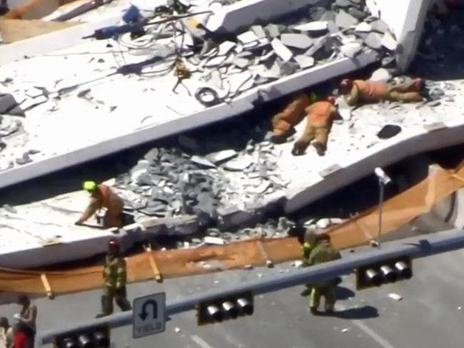 Rescuers crawled under the rubble in an effort to save people crushed after the bridge flattened cars on the highway at Florida International University. Picture: Twitter @NBCNews