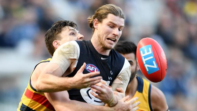 Jake Lever of the Crows tackles Bryce Gibbs of the Blues.