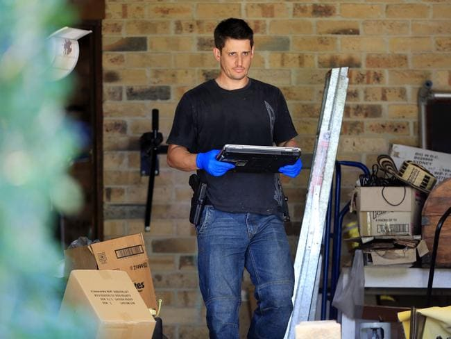 Police take away a laptop from the family home. Picture Craig Greenhill