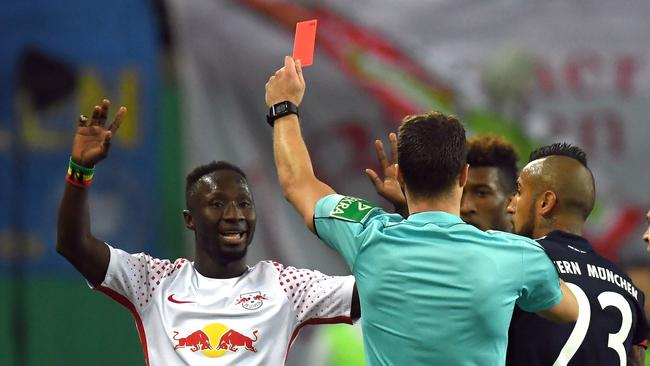 Referee Felix Zwayer shows Leipzig's Guinean midfielder Naby Keita (L) the red card during the German Cup football match RB Leipzig v FC Bayern