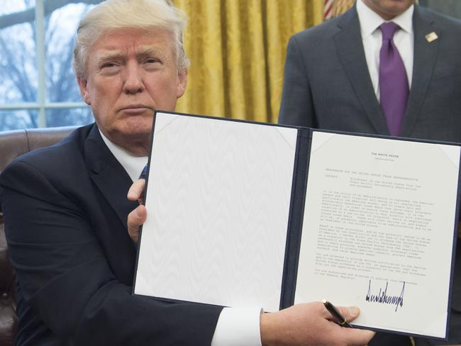 President Donald Trump holds up an executive order withdrawing the US from the Trans-Pacific Partnership with his distinctive spiky signature on the bottom. Picture: Saul Loeb/AFP.