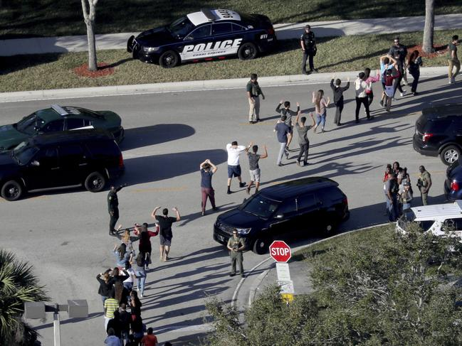 Students hold their hands in the air as they are evacuated by police from Marjory Stoneman Douglas High School in Parkland, Florida after a shooter opened fire on campus. Pic: AP