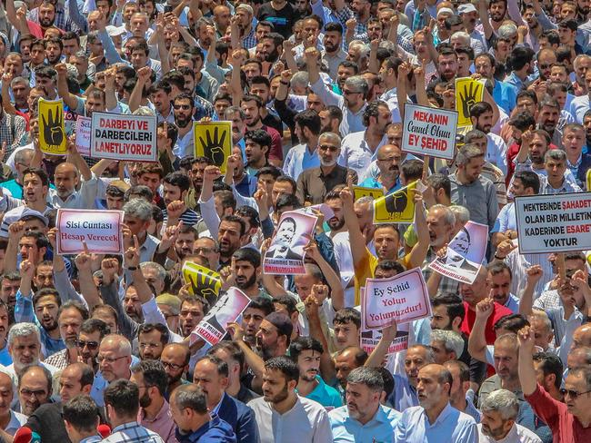 Men hold pictures of the former Egyptian president during a symbolic funeral prayer in Diyarbakir, in the Kurdish-majority southeast of Turkey. Picture: Ilyas Akengin / AFP