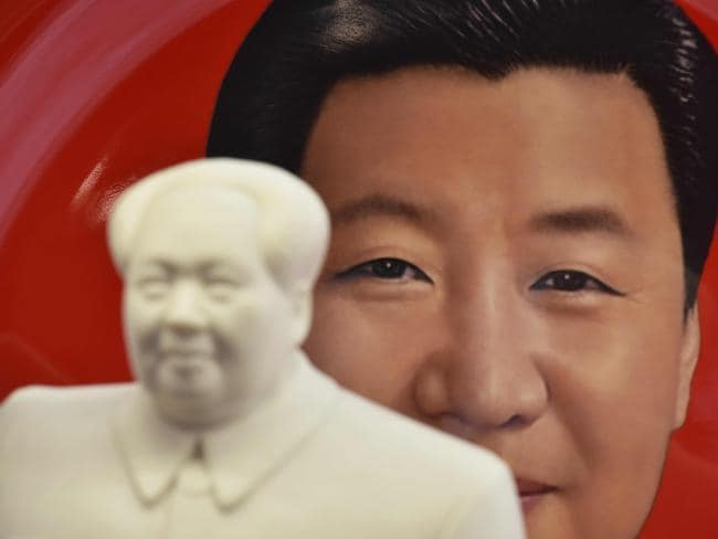 A decorative plate featuring an image of Chinese President Xi Jinping is seen behind a statue of late communist leader Mao Zedong at a souvenir store next to Tiananmen Square in Beijing. Picture: AFP