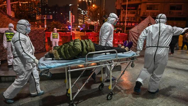 Chinese medical staff with a Covid-19 patient in Wuhan in January. Picture: AFP
