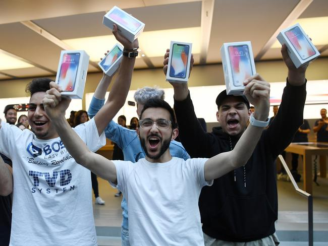 Mazen Kourouche, centre, one of the first purchasers of the iPhone X, stands with others as they show off their boxed phones to the media after its release to the public outside the Apple Store in Sydney. Picture: AAP