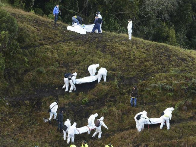Rescue workers carry the bodies of victims after the plane crashed in a mountainous area outside Medellin, Colombia.
