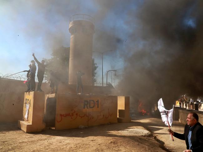 Protesters burn property in front of the US embassy compound, in Baghdad, Iraq. Picture: AP