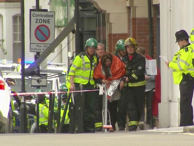 A woman with blankets wrapped around her is escorted by emergency services near the scene of an explosion in London. Picture: AP