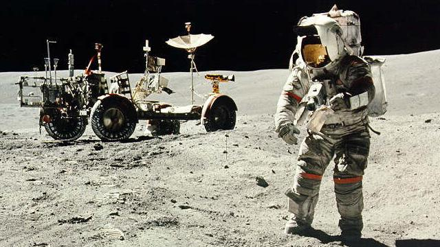 Apollo 16 astronaut Charles Duke in front of the rover vehicle on the surface of the moon.