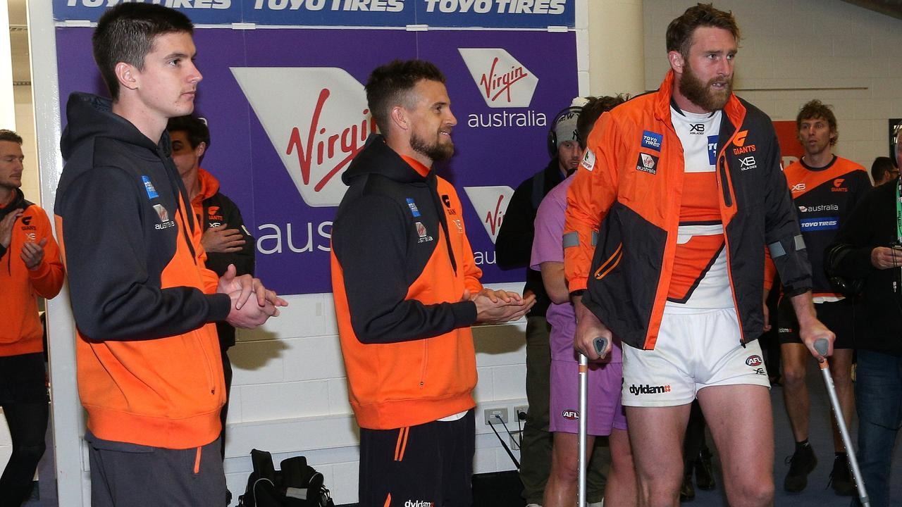 Sam Taylor, Brett Deledio and Dawson Simpson of the Giants injured after Carlton.