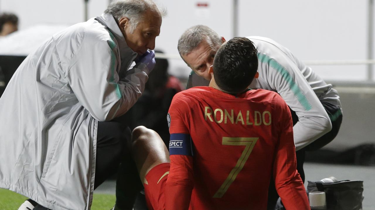Portugal's Cristiano Ronaldo receives treatment from medical staff during the Euro 2020 group B qualifying soccer match between Portugal and Serbia at the Luz stadium in Lisbon, Portugal, Monday, March 25, 2019. (AP Photo/Armando Franca)