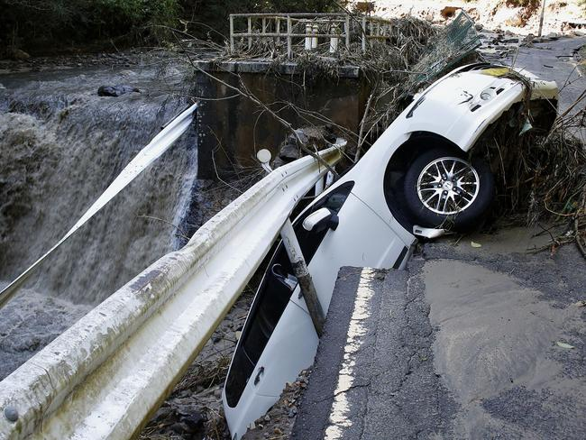 A vehicle falls off collapsed road in the typhoon-hit Kakuda city, Miyagi prefecture, northern Japan. Picture: Kyodo News via AP