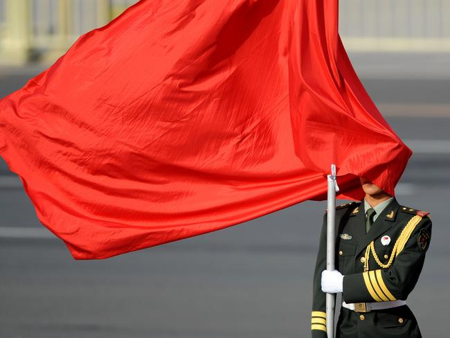 The winds blows a red flag on a Chinese honour guard's face as he stands guard before Sri Lankan President Mahinda Rajapaksa and Chinese President Xi Jinping. Picture: AFP