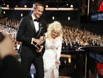 "Alexander Skarsgard accepts the award for outstanding supporting actor in a limited series or a movie for ""Big Little Lies"", left, from Dolly Parton on the red carpet stage at the 69th Primetime Emmy Awards on Sunday, Sept. 17, 2017, at the Microsoft Theater in Los Angeles. Picture: AP"