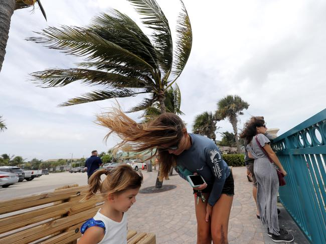 Locals face the wind and rain in Florida. Picture: AP