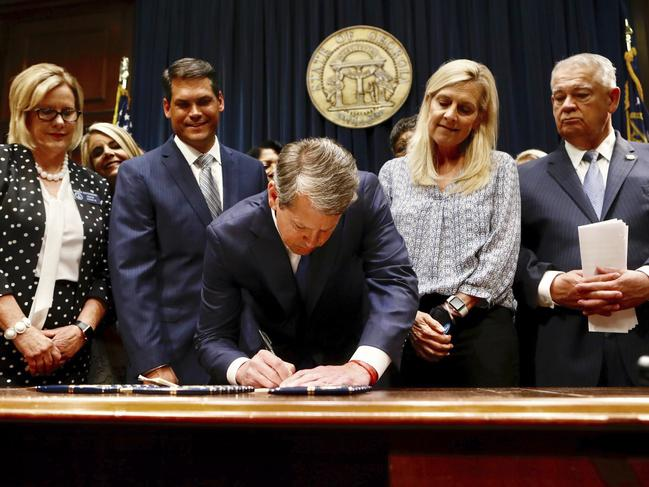 Georgia's Republican Governor Brian Kemp, centre, signs legislation. Picture: AP