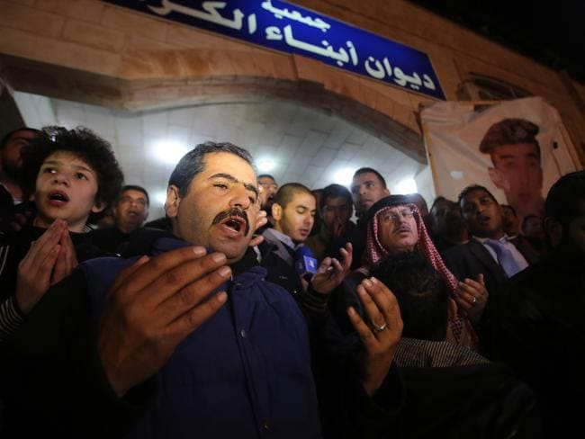 Shocked ... Supporters and family members of Jordanian pilot Maaz al-Kassasbeh pray following his reported killing, at the Karak tribal gathering chamber. Picture: AFP /STR