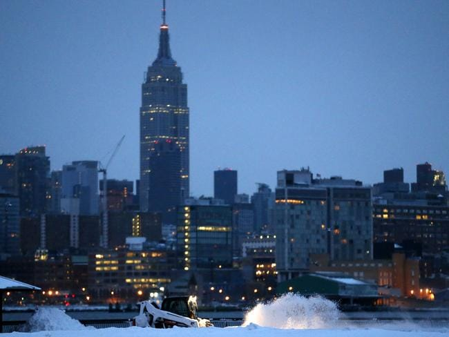 Back to business ... A person drives a sweeper while brushing snow off a walking path in Hoboken, New Jersey with the New York City skyline in the background. Picture: AP