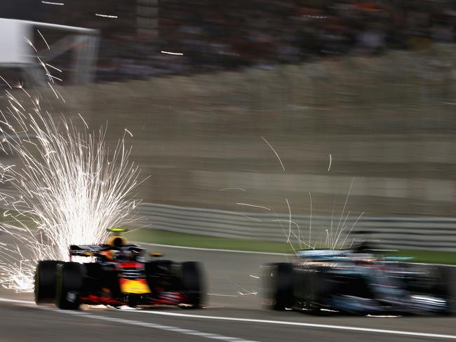 Sparks fly behind the cars of Max Verstappen and Lewis Hamilton at the Bahrain GP.