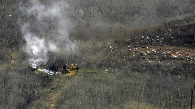 Firefighters work the scene of a helicopter crash. NBA basketball legend Kobe Bryant, his teenage daughter were among nine people killed in the crash in Southern California. Picture: AP PhotoMark J. Terrill