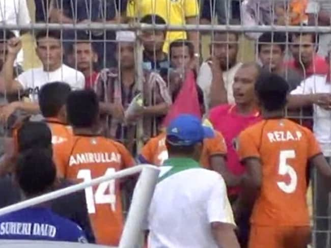 Players clash with the referee after the shocking tackle.