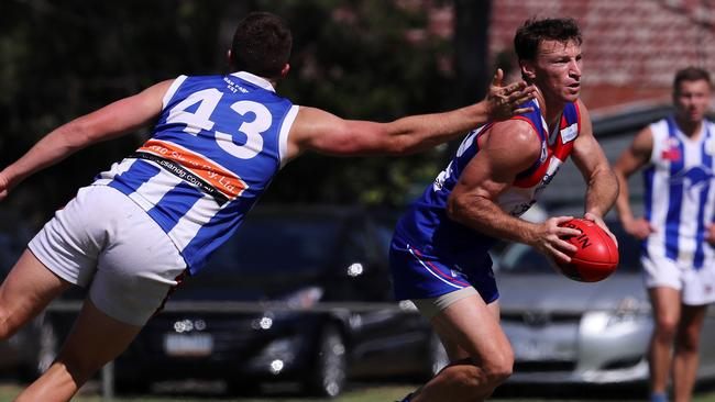 The retired North Melbourne Football Club legend shrugs off a tackle.