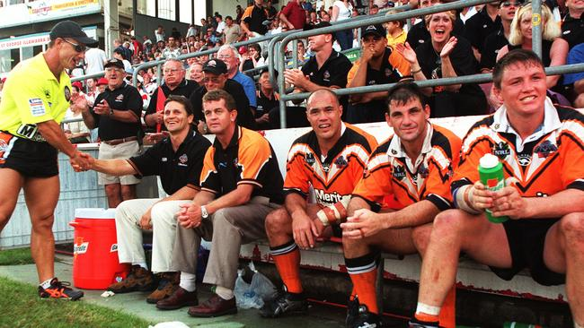 Wests Tigers coach Wayne Pearce sits on the bench with his team.