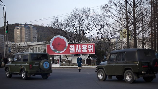 "A traffic policewoman, center, stands in the center of a junction near a sign, which reads ""Defend to the death"", as vans passing by in Pyongyang, North Korea."