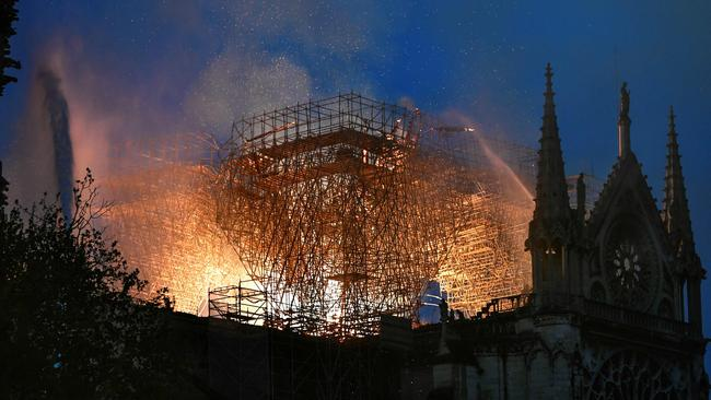 Flames are seen through the scaffolding of the Notre Dame. Picture: Stephane de Sakutin/AFP