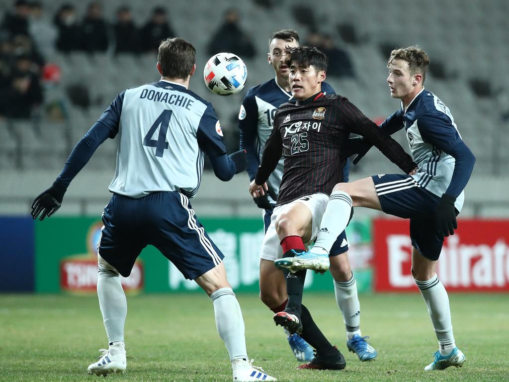Han Chan-hee of FC Seoul competes for the ball with a couple of Victory players.