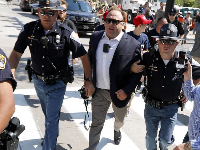 US radio host and conspiracy theorist Alex Jones, centre, has been banned by top tech companies for violating their hate content policies. Picture: AP Photo/John Minchillo, File