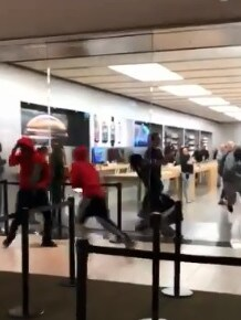 The group of six men run from the Apple store with the stolen goods in their arms.