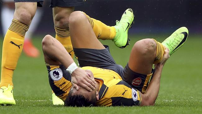 Arsenal's Alexis Sanchez holds his right ankle after sustaining an injury.