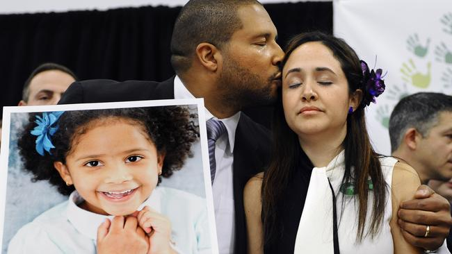 Jimmy Greene, left, kisses his wife Nelba Marquez-Greene as he holds a portrait of their daughter, Sandy Hook School shooting victim Ana Marquez-Greene on January 14, 2013. Picture: AP /Jessica Hill.