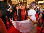 Karl Stefanovic bends down to adjust the dress of Lisa Wilkinson as she arrives at the 2015 Annual Logie Awards. Picture: Getty