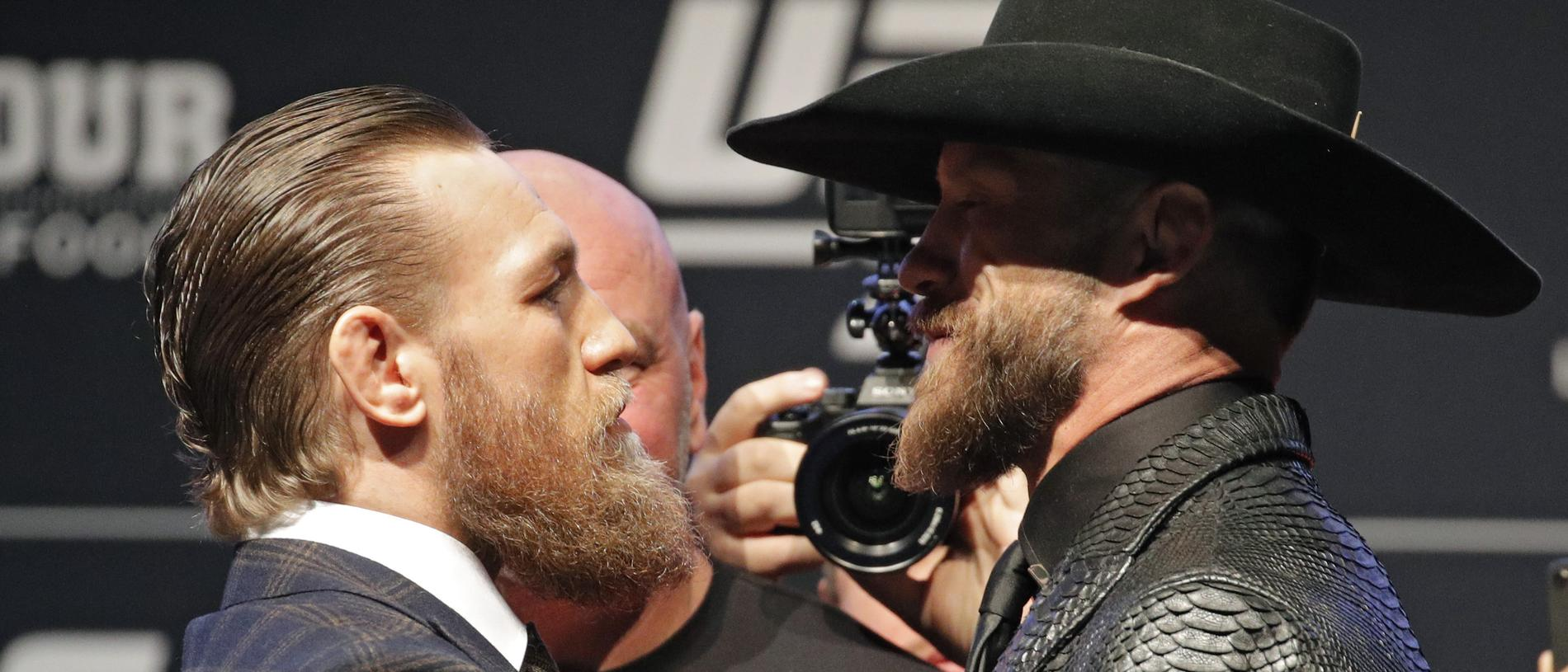 """Conor McGregor, left, and Donald """"Cowboy"""" Cerrone pose for photographers during a news conference for a UFC 246 mixed martial arts bout, Wednesday, Jan. 15, 2020, in Las Vegas. The two are scheduled to fight in a welterweight bout Saturday. (AP Photo/John Locher)"""