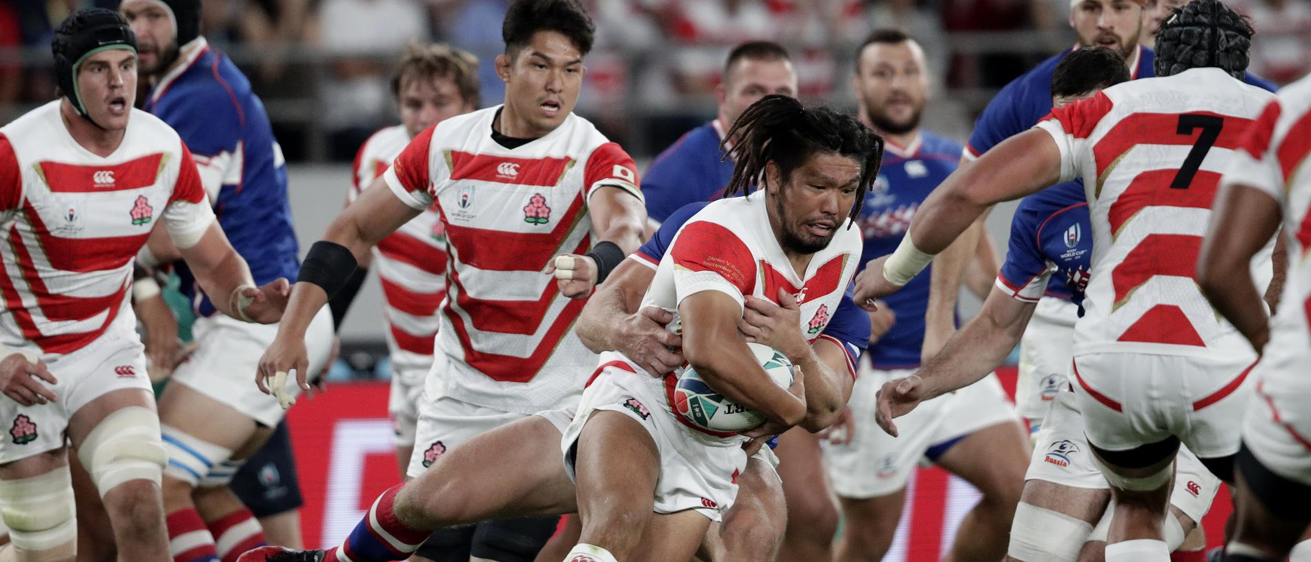 Japan's Shota Horie, centre, is tackled by a Russian player during the Rugby World Cup Pool A game at Tokyo Stadium between Russia and Japan in Tokyo, Japan, Friday, Sept. 20, 2019. (AP Photo/Jae Hong)