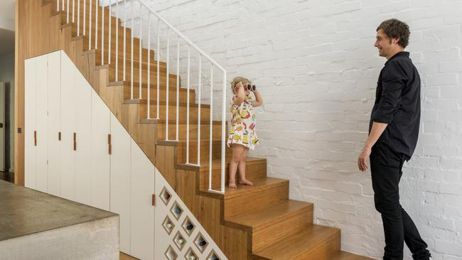 The under-stairs joinery includes holes for wine bottles and also …