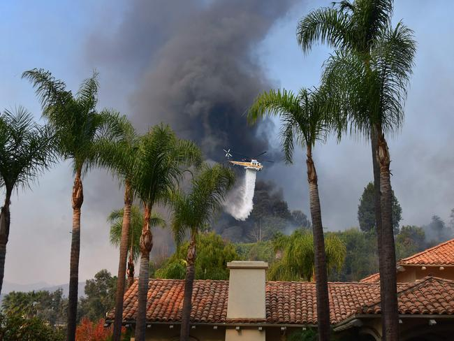 A helicopter drops water over burning homes in the celeb haven of Bel Air. Picture: AFP/Frederic J Brown