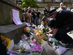 Police officers relocate floral tributes in St Ann's Square in Manchester, northwest England on May 23, 2017, laid as a mark of respect to those in killed and injured following a deadly terror attack at the concert at the Manchester Arena the night before. Picture: AFP