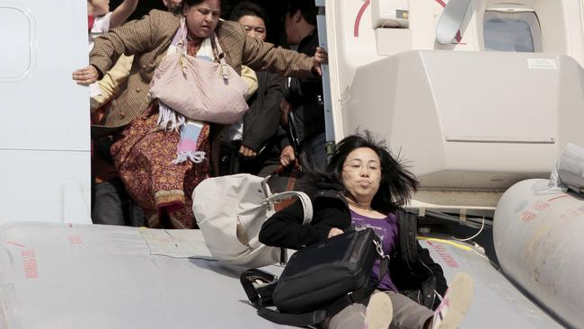 Experts say the trend of passengers grabbing their bags in an emergency is one of the greatest dilemmas facing cabin crew and airlines. Picture: AFP
