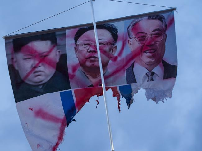 A banner showing the defaced photos of North Korean leaders Kim Jong-un, Kim Jong-il, and Kim Il-sung is displayed during a rally against a performance by North Korean musicians in Seoul. Picture: Jenni Lim/AFP
