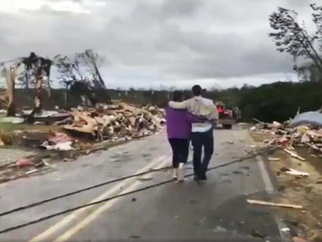 People walk amid debris in Lee County after what appeared to be a tornado struck in the area. Picture: AP