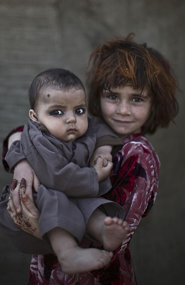 Afghan refugee girl, Khalzarin Zirgul, 6, holds her cousin, Zaman, 3 months, as they pose for a picture, while playing with other children in a slum on the outskirts of Islamabad, Pakistan.