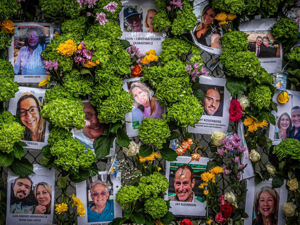 A memorial featuring photos of some of those lost in the partially collapsed 12-story Champlain Towers South building can be seen in Surfside, Florida.