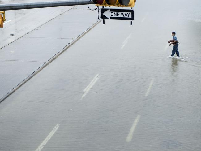 A man walks across a partially flooded street in Houston. Picture: Brendan Smialowski/AFP