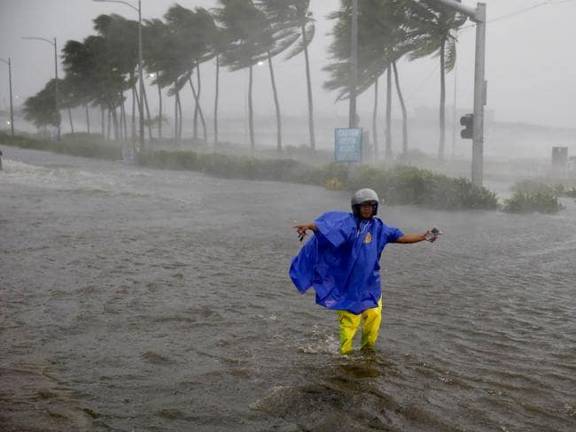 A traffic enforcer gestures at motorists to avoid a flooded street at the onslaught of Typhoon Mangkhut which barrelled into the northeastern Philippines before dawn Saturday. Picture: AP