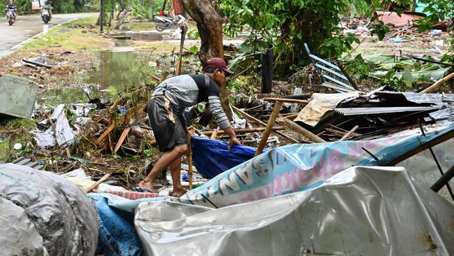 An Indonesian man looks for the body of a relative at a damaged house in Sukarame village in Carita, Banten province.