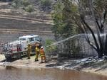 Firefighters make use of nearby water to battle the Sampson Flat bushfire. Picture: Roger Wyman